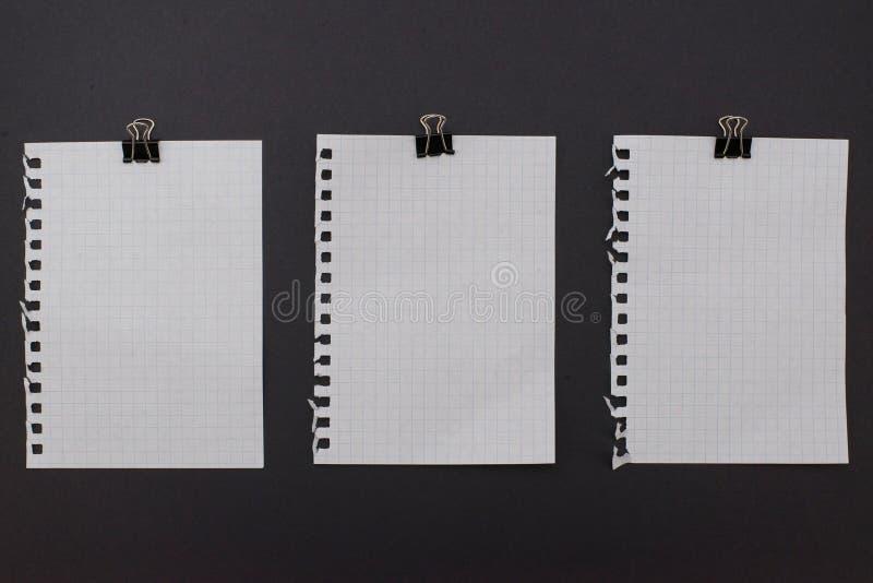 Drie witte blocnotebladen met zwarte metaalpaperclips op royalty-vrije stock afbeelding