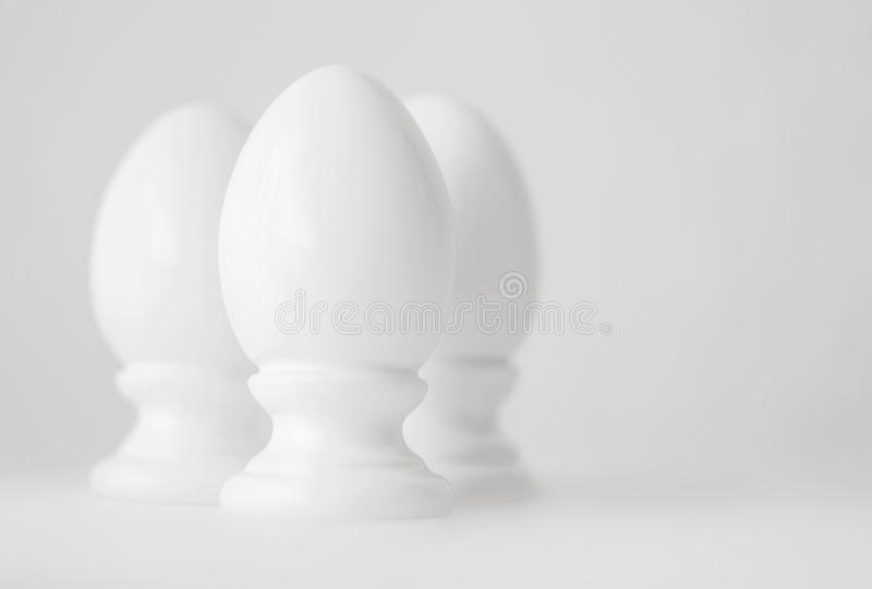 Drie witte decoratieve ceramische eieren op tribunes of in egg-cups op witte vage achtergrond Het godsdienstige Christelijke symb royalty-vrije stock afbeelding