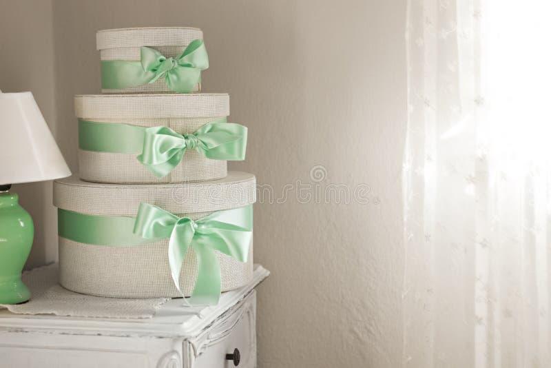 Drie witte dozen natuurlijke stof bevinden zich op elkaar gebonden met een groene boogtribune op een grijze oppervlakte royalty-vrije stock afbeeldingen