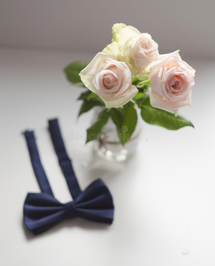 Drie witte rozen en vlinderdas Witte achtergrond royalty-vrije stock afbeeldingen