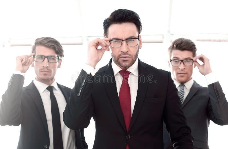 Drie zakenlieden met glazen, het aanmatigende bekijken de camera royalty-vrije stock foto