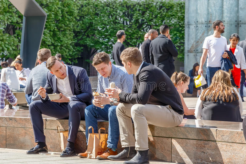 Drie zakenlieden op hun middagpauze in Cabot Square, Canary Wharf stock foto's
