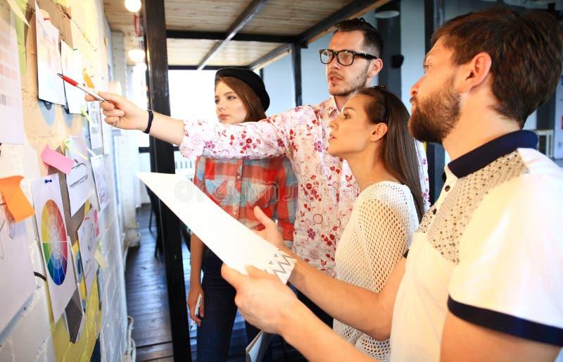 Drie zakenlui die en concept bespreken plannen Voorzijde van de teller en de stickers van de glasmuur royalty-vrije stock afbeelding