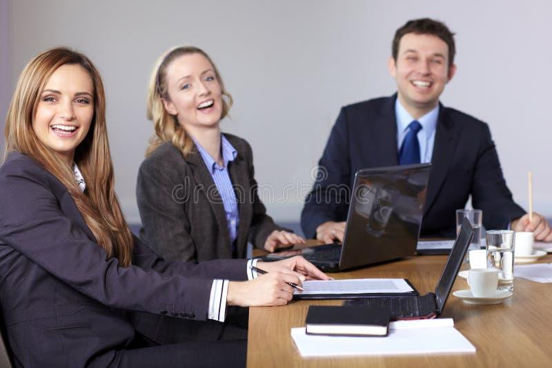 Drie zeer gelukkige bedrijfsmensen die bij lijst zitten royalty-vrije stock foto's