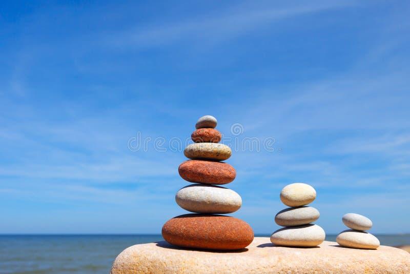 Drie Zen piramide van evenwichtige stenen op een achtergrond van het de zomeroverzees en de blauwe hemel stock fotografie