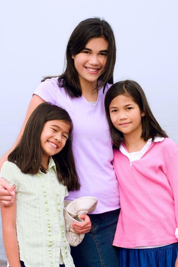 Drie zusters samen op mistig strand royalty-vrije stock afbeelding