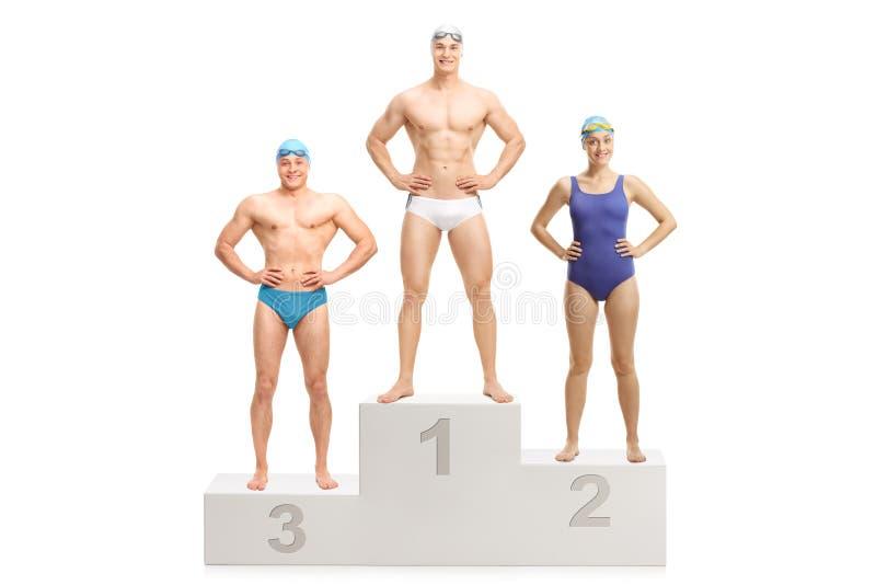 Drie zwemmers op een winnaar` s voetstuk voor eerst tweede en derde royalty-vrije stock afbeelding
