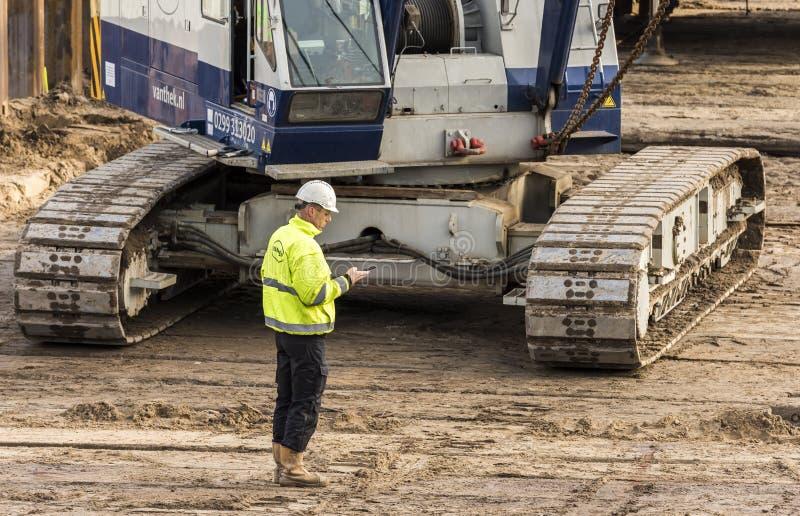 Construction Site Worker Calling Driebergen Station. Driebergen, Netherlands - November 26, 2017: Construction site at the railway station in Driebergen stock photography