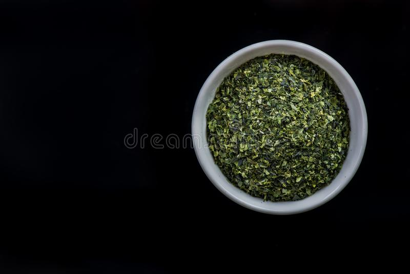 Dried aonori seaweed flakes in pot on dark stock image