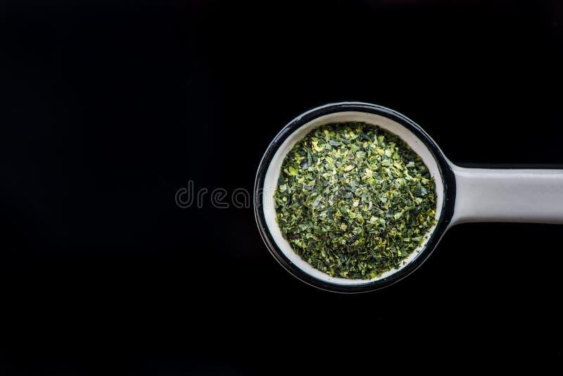 Dried aonori seaweed flakes on spoon stock photos