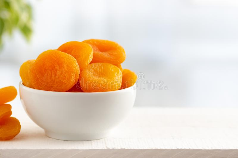 Dried apricots in a bowl on white wooden table. Concept healthy food, vegetarianism, diet. Copy space. Light background royalty free stock image