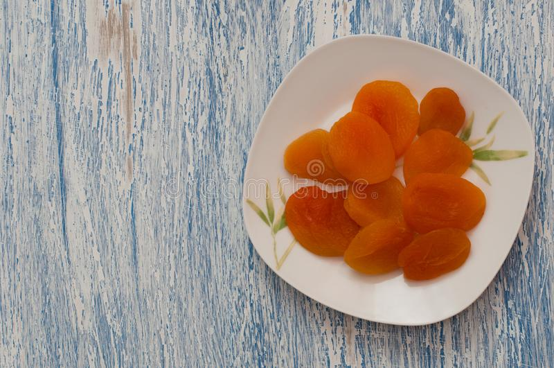 Dried apricots in a white plate on a white blue wooden table royalty free stock image