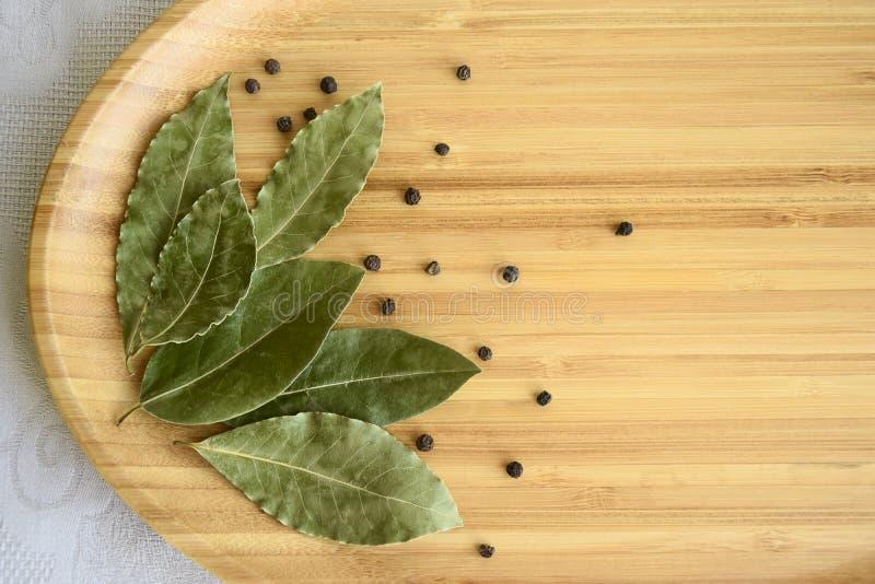 Dried bay laurel leaves, black peppercorns royalty free stock image