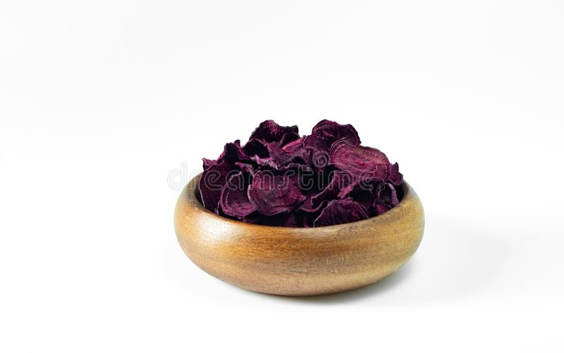 Dried beet chips in a wooden bowl on a white background. Vegetarian diet food. Horizontal orientation with copy space royalty free stock images