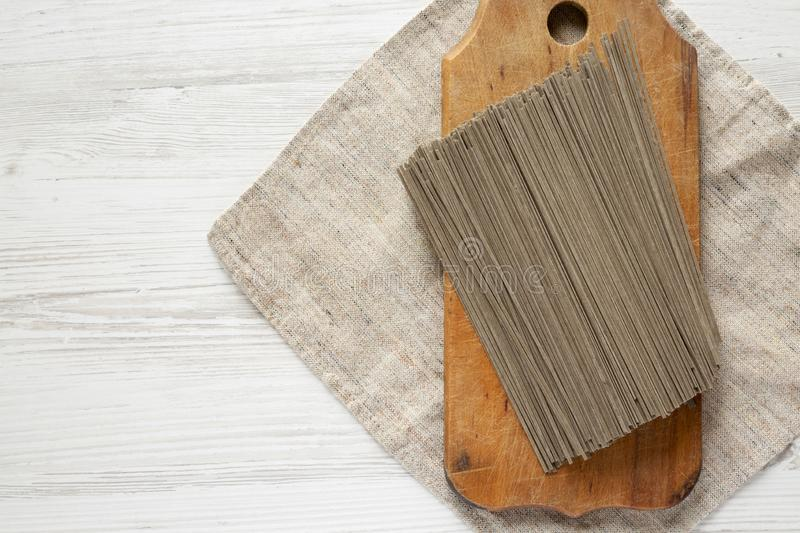 Dried buckwheat soba noodles on rustic wooden board over white wooden background, top view. Copy space royalty free stock image