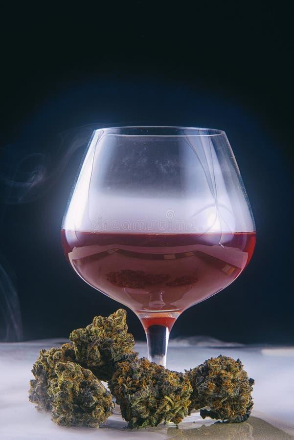 Dried cannabis buds Grandaddy Purple strain with glass of red. Detail of dried cannabis buds Grandaddy Purple strain with glass of red wine - infused medical stock image
