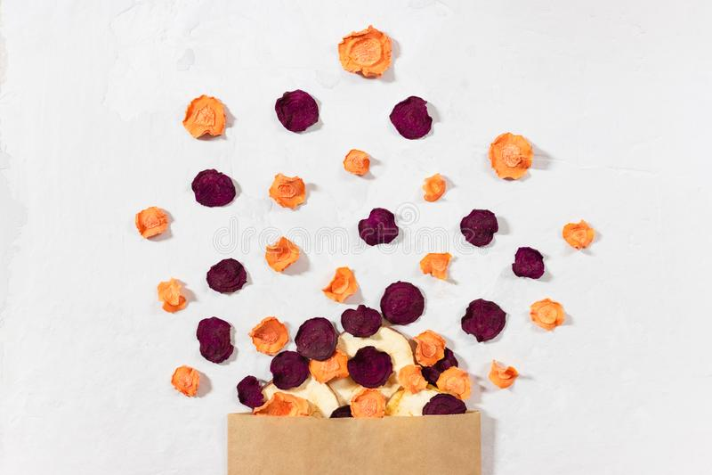 Dried carrot, beet, apple chips in a paper bag on a white concrete background. Organic natural food royalty free stock photography