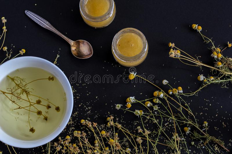 Dried chamomile in a tea cup and scattered on the background together with 2 small jars of honey. royalty free stock photo