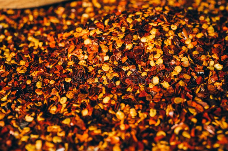 Dried chili flakes on wooden background. Close up view of crushed red cayenne pepper. Top view of red chili flakes as texture. royalty free stock photo