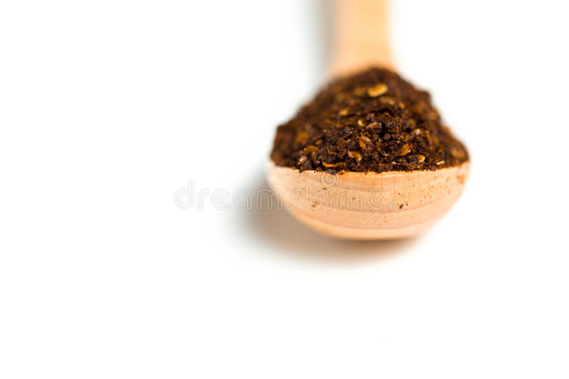 A dried chili flakes in a wooden spoon. Isolated over white background stock photo