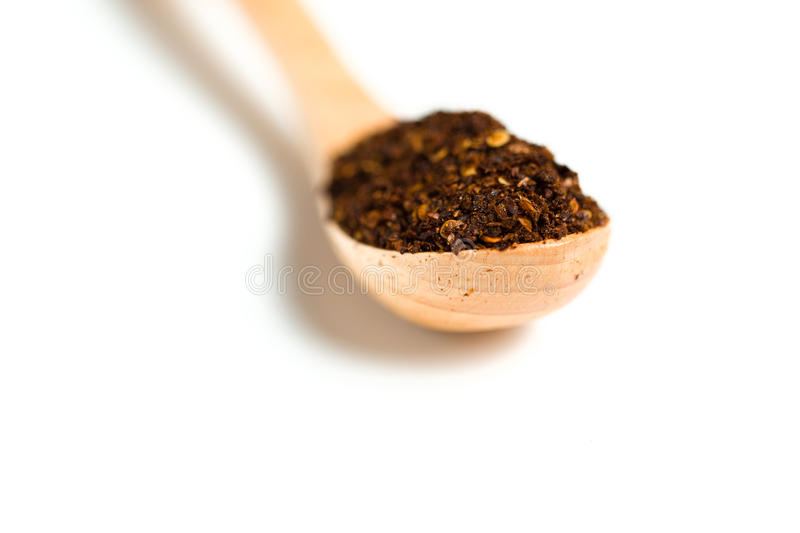 A dried chili flakes in a wooden spoon. Isolated over white background stock photos