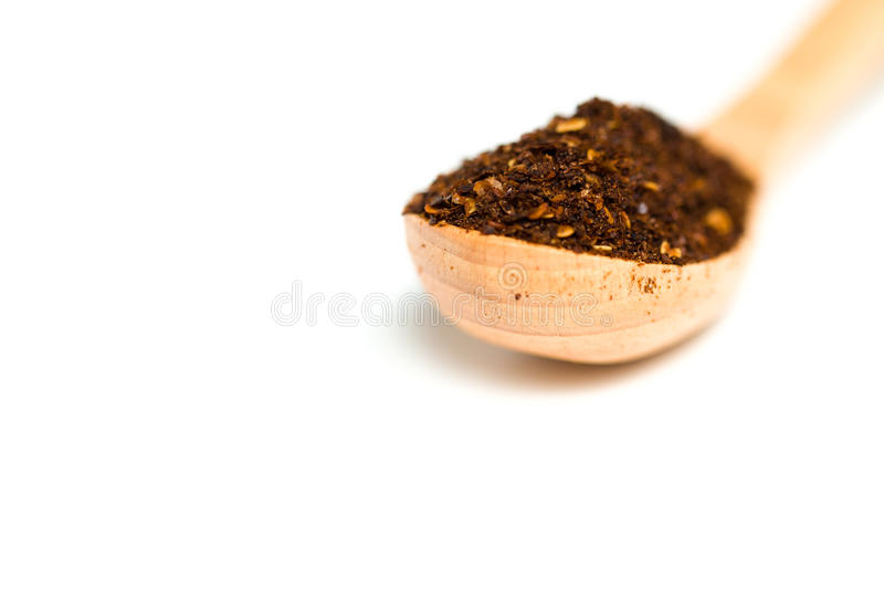 A dried chili flakes in a wooden spoon. Isolated over white background royalty free stock image