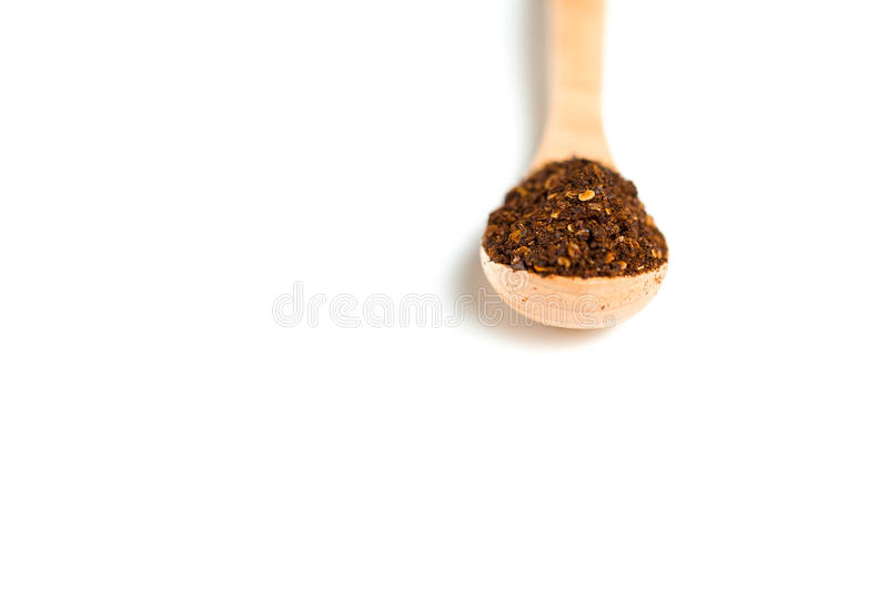 A dried chili flakes in a wooden spoon. Isolated over white background stock photography