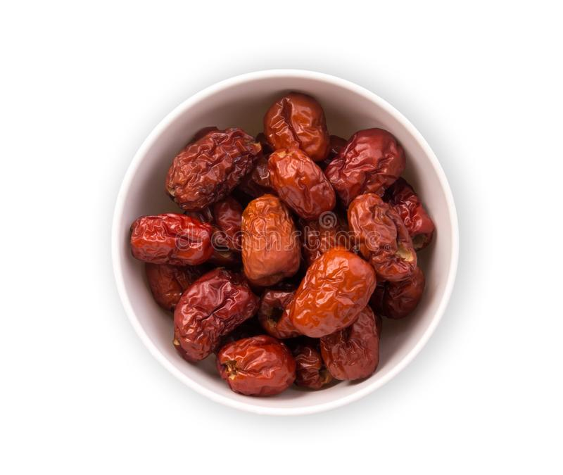 Dried chinese red jujube in the white bowl isolated on white background, top view, stock photography