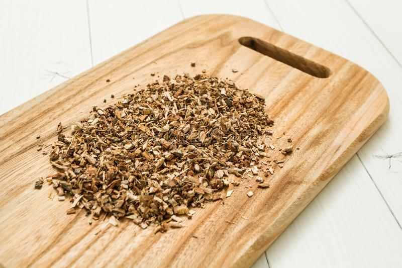Dried chopped oak bark on a wooden board, homeopathy royalty free stock photography