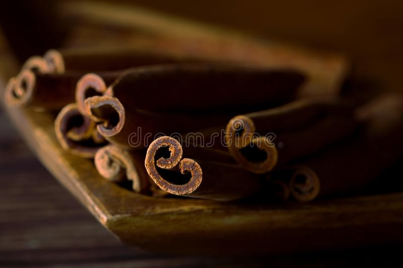 Dried cinnamon sticks in wooden bowl on rustic wooden table - selective focus royalty free stock photography