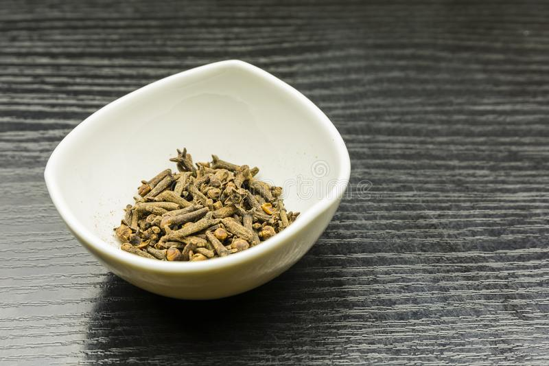 Dried cloves in a bowl. Dried cloves in a bowl on a wooden table stock photo