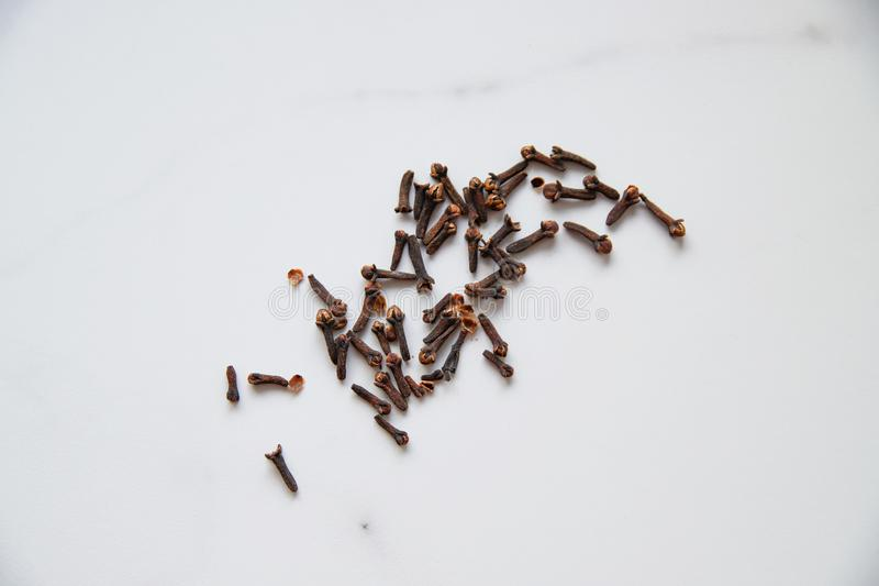 Dried cloves on grey marble background. Spice for hot tea, winter drinks and food stock photos
