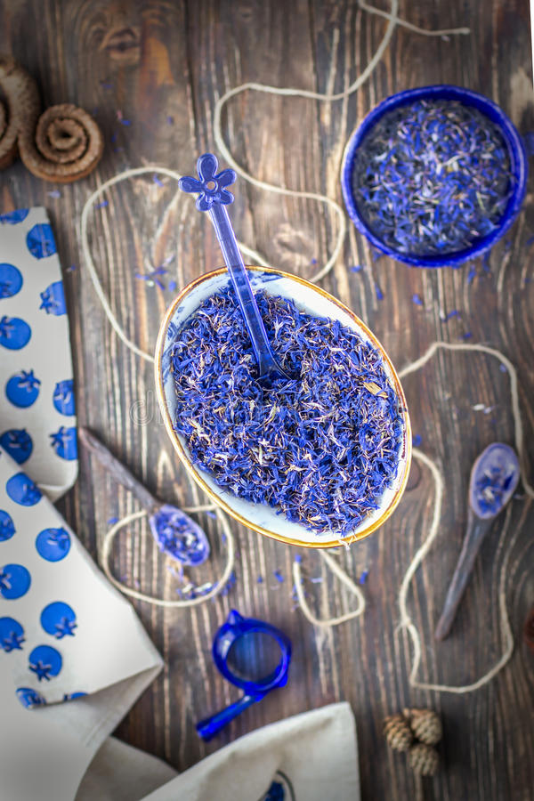 Dried cornflower petals on wooden background. Top view royalty free stock image