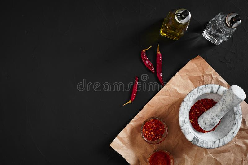 Dried and crushed red chili pepper in stone mortar. Copy space royalty free stock photo
