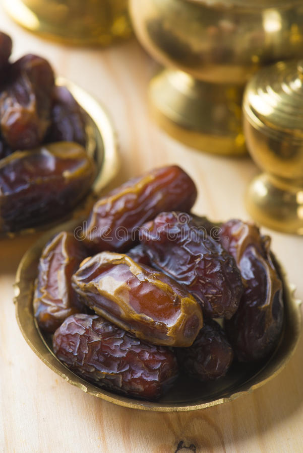 Free Dried Date Palm Fruits Or Kurma, Ramadan Food Which Eaten In Fasting Month. Pile Of Fresh Dried Date Fruits In Golden Metal Bowl. Stock Image - 34454101