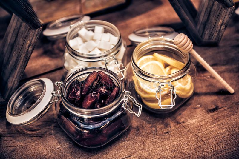 Dried dates, cuted lemons, sugar in glass food containers and honey stick for tea on wooden vintage coffee table. stock images