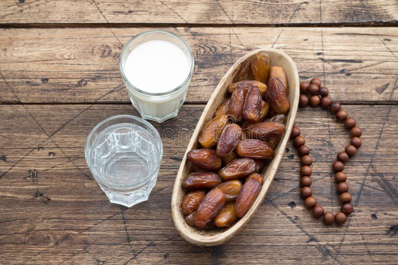 Dried dates fruits on a branch, a glasses of water and milk on a wooden table stock photography