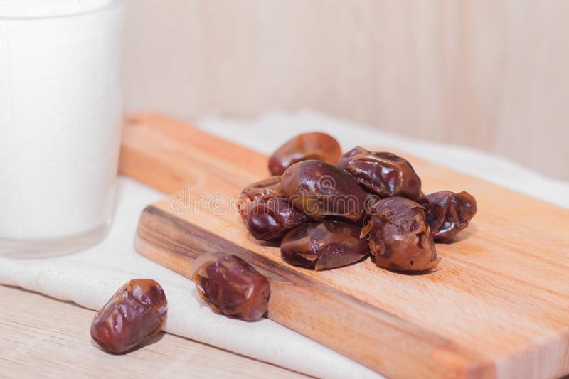 Dried dates, milk on fabric background. concept. Dates wooden board. Vegetarian food. Copy space. royalty free stock photography
