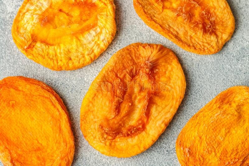 Dried delicious peaches on a gray concrete or stone background. An ingredient for making sweet dishes. Useful fruit. Healthy snack. Selective focus, top view stock photography