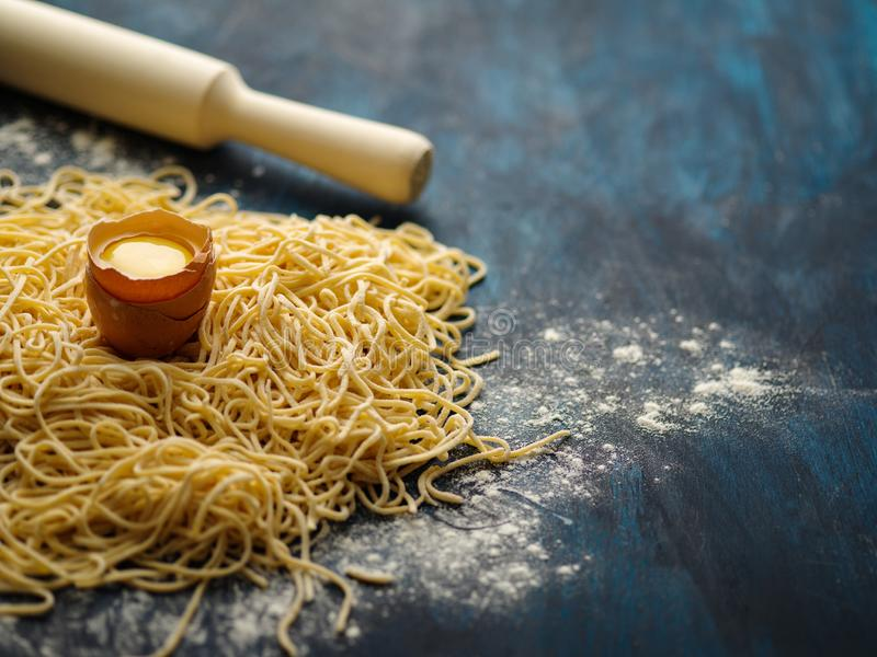 Dried egg noodles. Raw Fresh Spaghetti on blue wooden background stock image