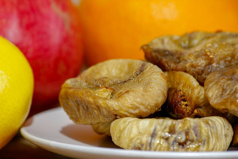 Dried fig on white ceramic plate. On wooden table with various of citrus in the background royalty free stock image