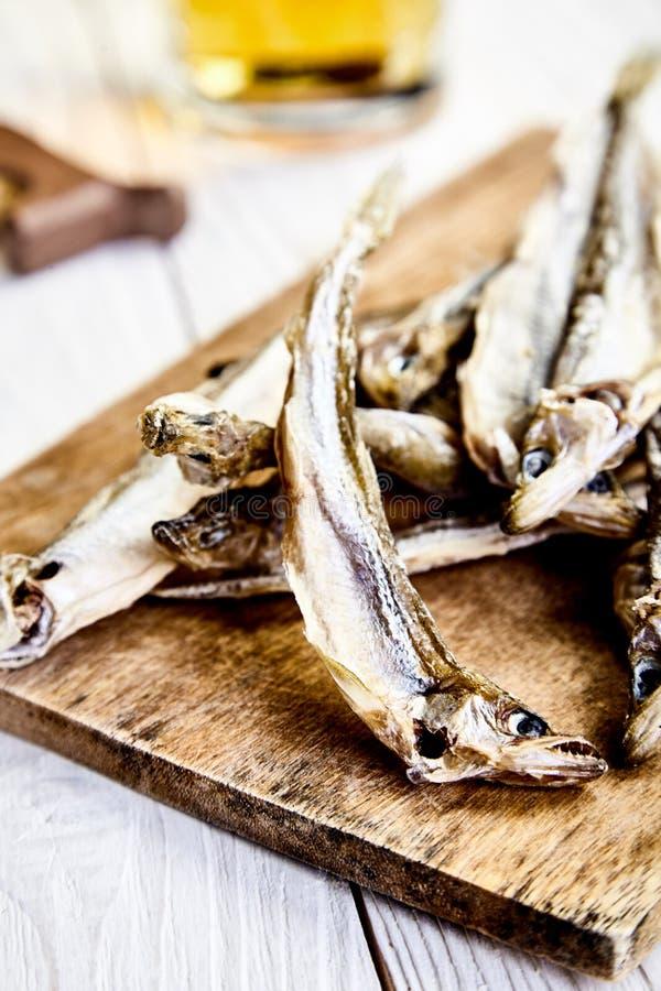 Dried fish on chopping board, mug of beer behind stock images