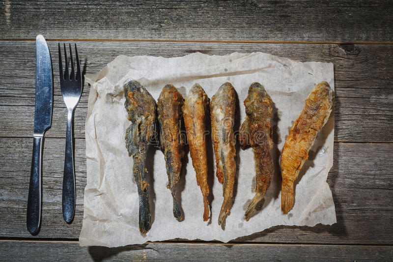 Dried fish with fork and knife on the table. Salty dry river fish on a wooden impressive background. Sun dried fish. Stock-fish. royalty free stock photo