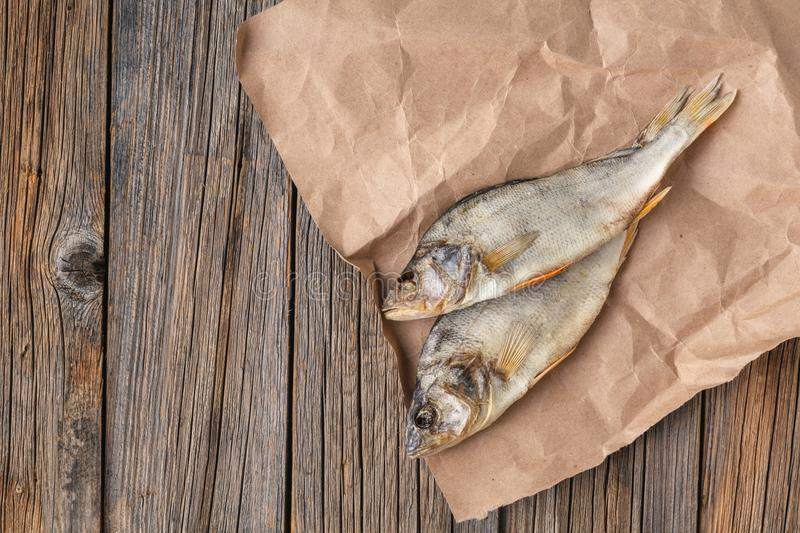 Dried fish on the table. Salty dry river fish on a dark wooden b stock photography
