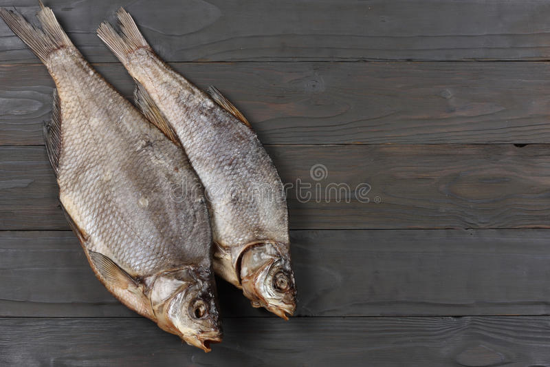 Dried fish on the table. Salty dry river fish on a dark wooden background.top view with copy space royalty free stock images