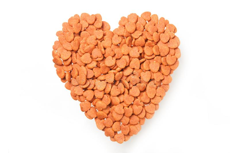Dried food for dog puppy, with a shape of heart isolated on whit stock image