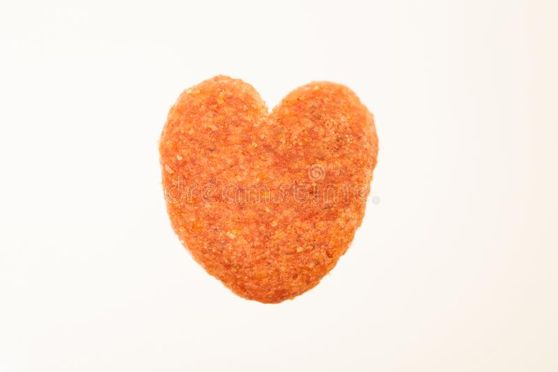Dried food for dog puppy, with a shape of heart isolated on whit stock photography