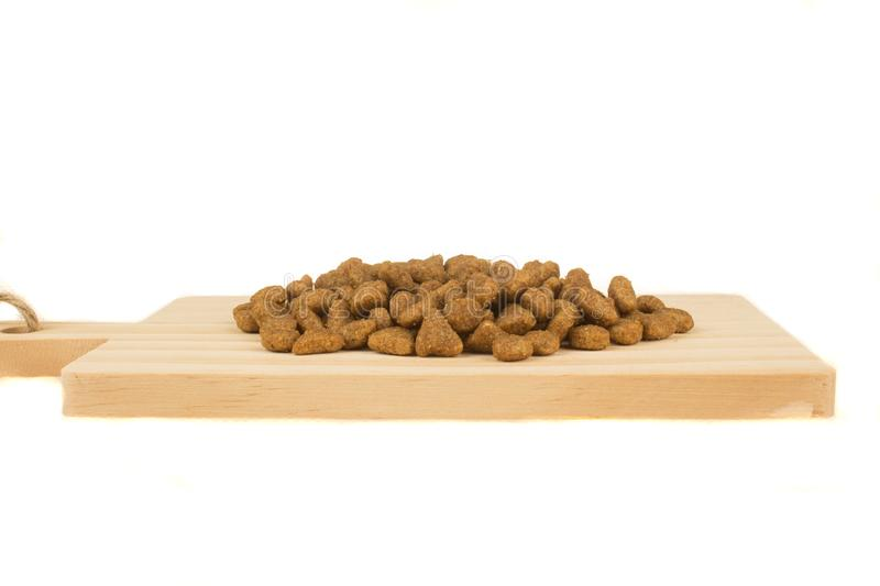 Dried food for dogs or cats on wooden cutting board. Pet care.  royalty free stock photo
