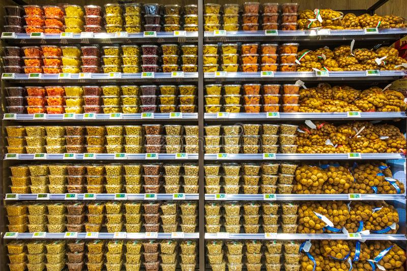 Dried fruit containers on shelves inside a supermarket. Multicolors. royalty free stock photo