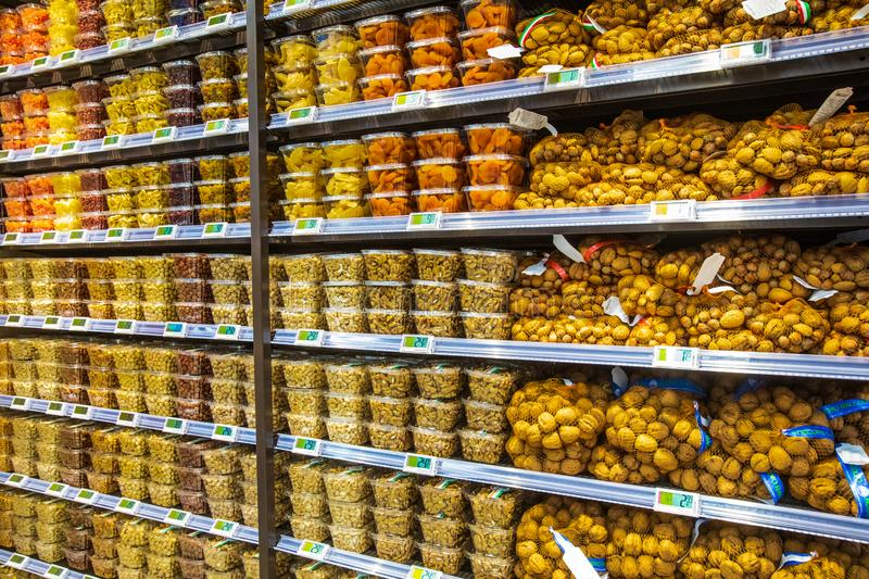 Dried fruit containers on shelves inside a supermarket. Multicolors. stock images